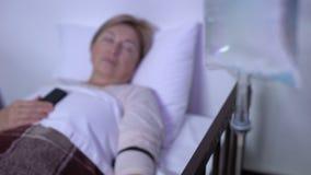 Primer contrario del descenso, paciente femenino maduro que duerme en lecho de enfermo con el teléfono metrajes