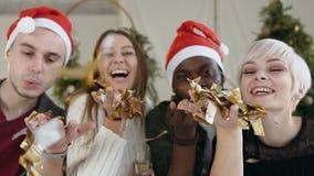 Primer Cuatro alegres de gente de la raza mixta están soplando un confeti de oro de las manos en la celebración de la Navidad o metrajes