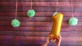 Primer cumpleaños feliz, balones de aire de oro con el número uno, celebración del aniversario almacen de video