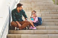 Primer día en la escuela el padre lleva a la colegiala del pequeño niño en f Foto de archivo libre de regalías