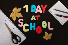 Primer día en la inscripción de la escuela hecha de letras, de fuentes de escuela y de hojas de otoño coloreadas en el fondo negr imágenes de archivo libres de regalías