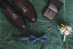 Primer de accesorios masculinos oscuros elegantes elegantes en fondo verde Vista superior de la corbata de lazo, zapatos, ramille Foto de archivo libre de regalías