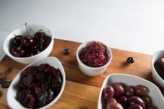 Primer de aceitunas con las diversas frutas en cuenco en tabla de cortar Foto de archivo libre de regalías