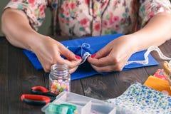 Primer de acolchar de costura de la mano de la mujer Imagenes de archivo
