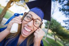 Primer de adolescente expresivo en el casquillo y el vestido que sostienen el diploma Fotografía de archivo