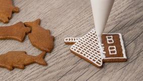 Primer de adornar un pan de jengibre de la Navidad en forma de la cabaña Fotos de archivo libres de regalías