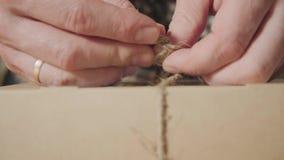 Primer de atar la guita en el arco embalaje del lazo de mariposa de los productos finales hecho de lanas Hombre joven apuesto metrajes