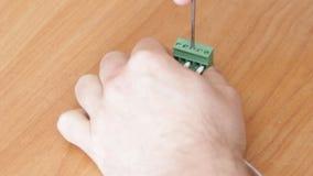 Primer de atornillar del trabajador del electricista de alambres metrajes
