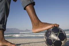 Primer de Barefeet con el balón de fútbol en la playa Fotografía de archivo libre de regalías