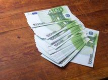 Primer de 100 billetes de banco euro en el fondo de madera Fotografía de archivo