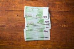 Primer de 100 billetes de banco euro en el fondo de madera Imágenes de archivo libres de regalías