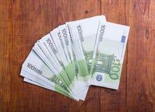 Primer de 100 billetes de banco euro en el fondo de madera Imagen de archivo