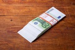 Primer de 100 billetes de banco euro en el fondo de madera Fotografía de archivo libre de regalías