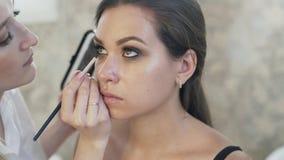 Primer de cámara lenta, el maquillaje del ojo, el artista de maquillaje pide el modelo para mirar para arriba, coge sombras oscur almacen de video