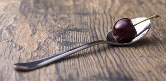 Primer de cerezas en una cuchara de plata en fondo marrón Imágenes de archivo libres de regalías