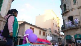 Primer de chicas jóvenes en los trajes verdes del carnaval que mueven encendido un coche grande del desfile con confeti Arte Niño almacen de video