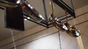 Primer de diversos utensilios de la cocina en el restaurante o el caf? que cuelga en una barra transversal negra del metal Cap?tu almacen de metraje de vídeo