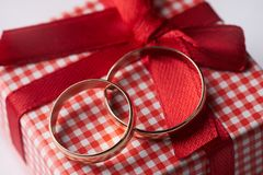 Primer de dos anillos de bodas del oro y cajas de regalo para casarse con el arco rojo Fotos de archivo libres de regalías