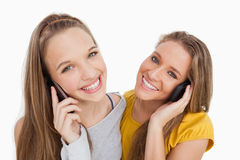 Primer de dos mujeres jovenes que sonríen en el teléfono Imagen de archivo