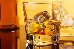 Primer de dos vidrios de whisky cerca de la botella en la tabla con la reflexión, atmósfera caliente Foto de archivo