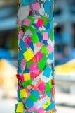Primer de etiquetas engomadas coloreadas en un pilar en la calle Foto de archivo