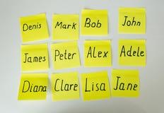 Primer de etiquetas engomadas de papel amarillas con los nombres masculinos y femeninos Fotografía de archivo libre de regalías