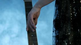 Primer de fingeres femeninos Una muchacha en un vestido del concierto se acerca al cuello de la guitarra y la pasa suavemente par metrajes