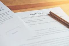 Primer de firmar un acuerdo y una pluma de la documentación en la tabla fotografía de archivo libre de regalías