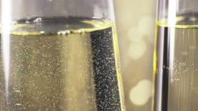 Primer de flautas de relleno del champán con las burbujas de oro contra el fondo del bokeh del oro, concepto de día de fiesta de  metrajes