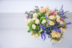 Primer de flores artificiales de rosas de la espuma de los colores del azul, blancos en un pote blanco y un ataúd de madera hecho Imagenes de archivo