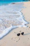 Primer de gafas de sol y del corazón en la playa tropical Foto de archivo libre de regalías
