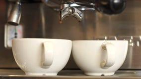 Primer de hacer el café caliente en una máquina del café, dos tazas de café almacen de metraje de vídeo
