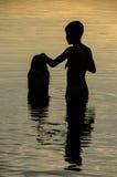 Primer de hermanos en el agua de un lago en la puesta del sol Imagen de archivo libre de regalías