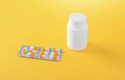 Primer de iconos de la medicación en un fondo amarillo brillante Ampollas brillantes con las cápsulas blancas y anaranjadas Fotografía de archivo