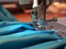 Primer de la aguja de la máquina de coser con la materia textil azul fotos de archivo libres de regalías