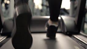 Primer de la aptitud de las zapatillas de deporte del pie que corre en la rueda de ardilla, piernas musculares en gimnasio metrajes