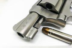 Primer de la bala en la munición estupenda 38 con una arma de mano en el fondo blanco Foto de archivo