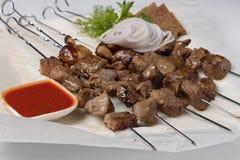 Primer de la barbacoa asada a la parrilla con el calabacín, la salsa y las patatas fritas cocidos imágenes de archivo libres de regalías