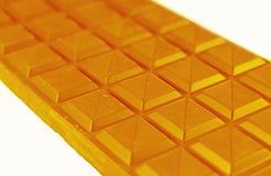 Primer de la barra de chocolate en Honey Yellow Color Isolated en el fondo blanco Fotografía de archivo libre de regalías