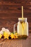 Primer de la bebida de la vitamina en un tarro grande con una paja al lado del limón, del jengibre, y del carambola en un fondo d Foto de archivo