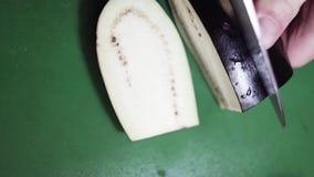 Primer de la berenjena que es cortada con el cuchillo afilado grande en la tabla de cocina verde almacen de video