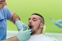 Primer de la boca abierta del paciente durante chequeo oral Foto de archivo libre de regalías