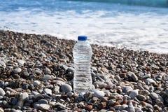 Primer de la botella del plástico transparente con el agua potable que se coloca en la playa con una opinión del mar Foto de archivo