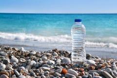 Primer de la botella de la opinión y del plástico del mar con agua en el fondo Imagen de archivo libre de regalías