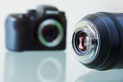 Primer de la cámara de la foto de DSLR y aún lente en el escritorio Fotografía de archivo libre de regalías