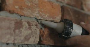 Primer de la cámara lenta de la costura de relleno del trabajador entre los ladrillos con el mortero del arma del sellante fotografía de archivo