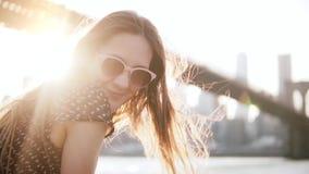 Primer de la cámara lenta del turista femenino europeo feliz en gafas de sol que sonríe en la cámara en el paisaje de Nueva York  almacen de metraje de vídeo
