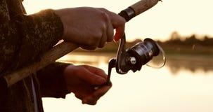 Primer de la caña de pescar del carrete de la fricción en el fondo de una puesta del sol hermosa almacen de video