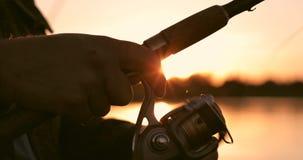Primer de la caña de pescar del carrete de la fricción en el fondo de una puesta del sol hermosa almacen de metraje de vídeo