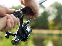 Primer de la caña de pescar en manos del pescador fotos de archivo